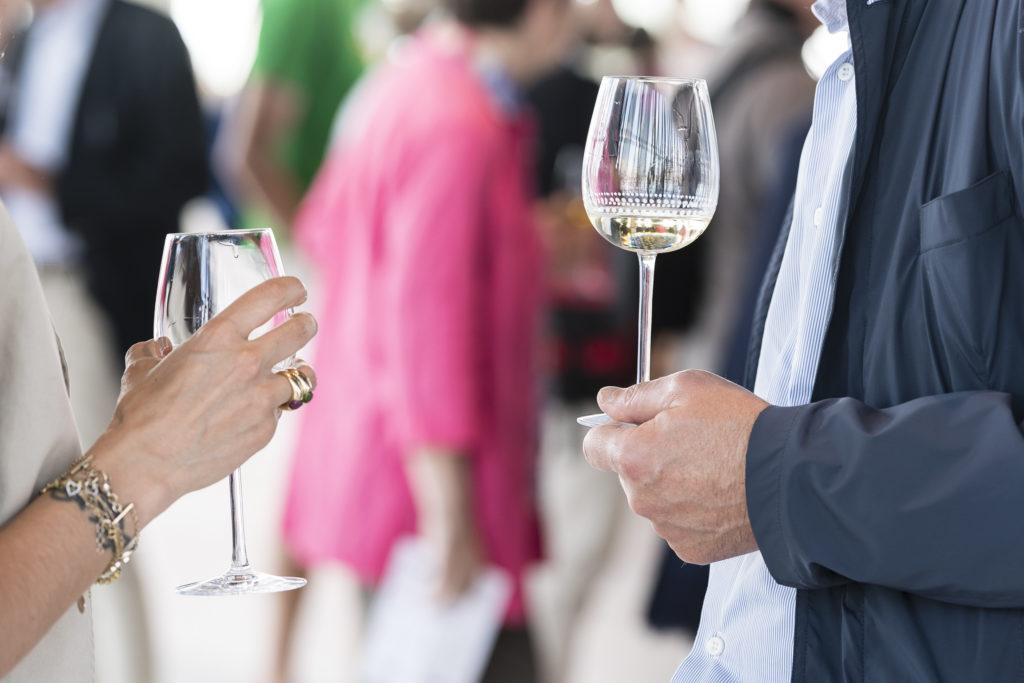 deux personnes face à face qui tiennent un verre de vin blanc